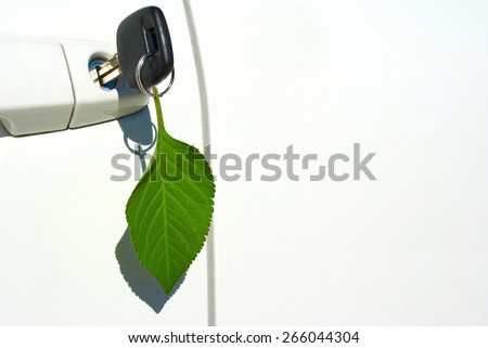 Environmentally friendly automobile with leaf key ring hanging from door - stock photo