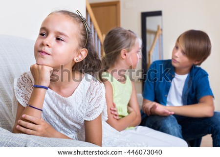 Envy little child sitting aside of boy and girl at home - stock photo