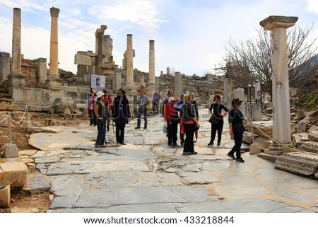EPHESUS, TURKEY - FEBRUARY 17, 2016: Tourists walk down the marble walkway in Ephesus, Turkey in the Middle East - stock photo