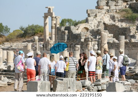 Ephesus, Turkey - June, 26, 2014: A group of tourists gather around a tour guide in the celsus library area of Ephesus in order to hear the guide tell them about the site. - stock photo