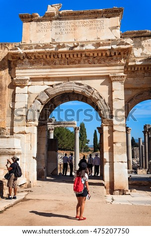 EPHESUS, TURKEY - SEPTEMBER 30, 2014: Woman Tourist with a guide book admires the Gate of Augustus in Efes