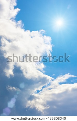 Epic blue sky with white fluffy clouds and sun. Sunny day