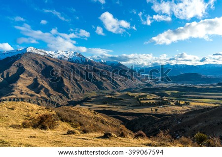 Epic mountain valley landscape. Aerial scenic valley view from Crown Range road, Queenstown, New Zealand. Mountain road to Queenstown. Beautiful mountain landscape - stock photo