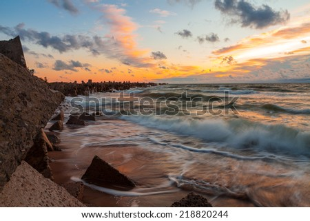 Epic sunset over the stormy Baltic sea with breakwater leading from foreground into horizon - stock photo