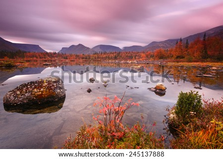 Epic view of Polygonal lake with lichen covered rocks and pebbles in water and juniper and ash tree in foreground, Hibiny mountains above the Arctic circle in Russia - stock photo