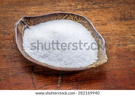 Epsom salts (Magnesium sulfate) in a leaf shaped ceramic bowl against rustic wood - relaxing bath concept - stock photo