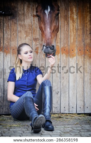 Equestrian girl and horse in stable - stock photo