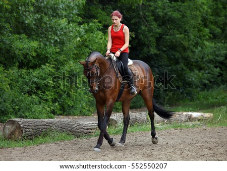 Equestrian girl horseback riding along forest trail