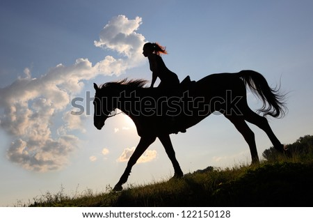 Equestrian girl horseback riding at sunset