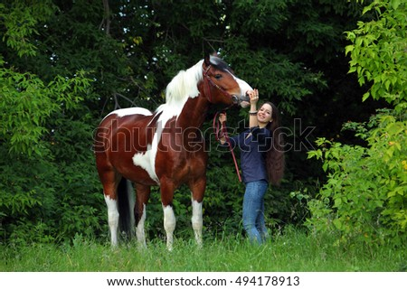 Equestrian model with her horse in summer nature