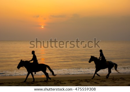 Equestrian on the beach sunset. Blur photo
