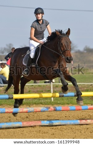 Equestrian sport: young girl in jumping show - stock photo