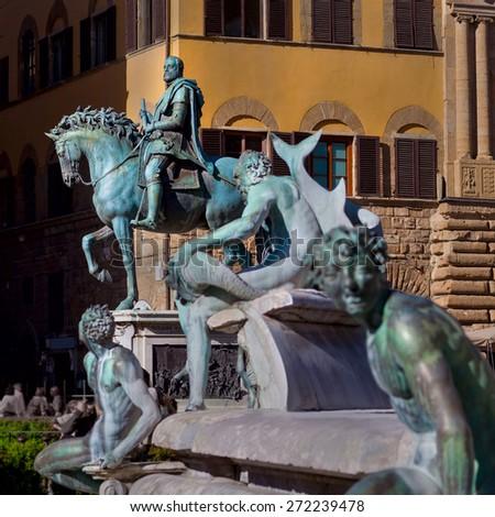 Equestrian statue of Cosimo I de' Medici on the Piazza della Signoria  in front of the Palazzo Vecchio. Fountain Neptune on a foreground.  Florence, Tuscany, Italy. - stock photo