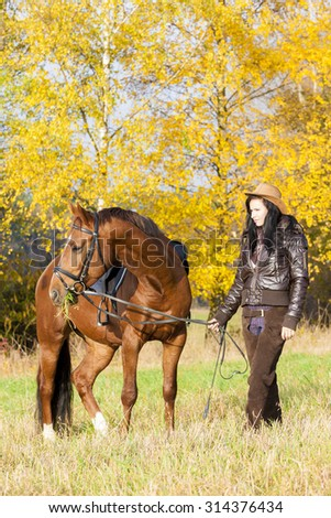 equestrian with her horse in autumnal nature - stock photo