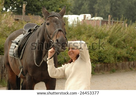 Equestrienne puts bridle on a horse. - stock photo