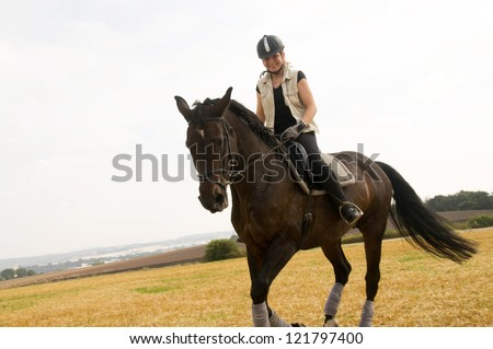 Equestrienne rides  across the field. - stock photo