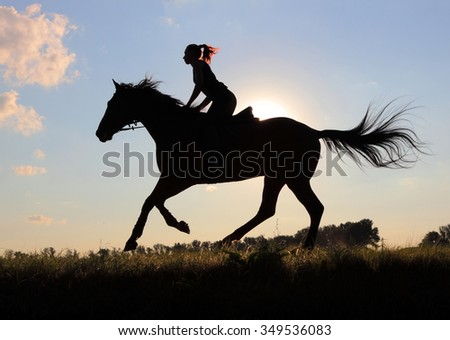 Equetsrian riding her hHorse at sunset