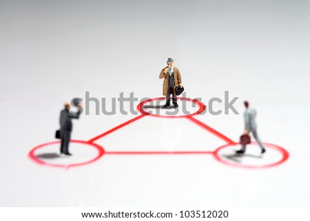 Equilateral triangle of tiny miniature businessmen with focus to the man in the rear in a teamwork, leadership and seniority concept
