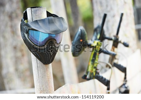 Equipment for paintball playing. Protective mask and gun paintballing marker in forest - stock photo