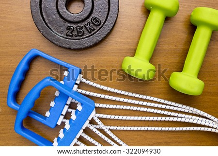 Equipment for sport - dumbbells, stretching expander and a portion of the stacked weights. - stock photo