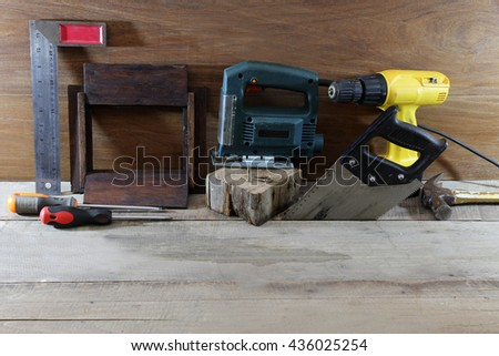 Equipment mechanic with saws, power saw, drill, screwdriver, screws, angle bar and wood picture frame on a wooden floor.