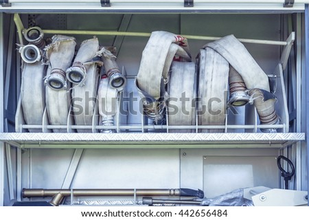 Equipment of Fire Truck: heavy duty water hoses in a firefighter vehicle - stock photo