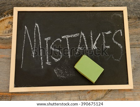 Erase or forget mistakes written in chalk on a chalkboard on a rustic background - stock photo
