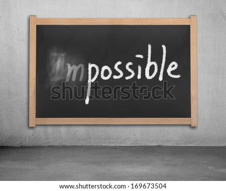 Erasing word impossible on black wooden chalk hanging on concrete wall - stock photo