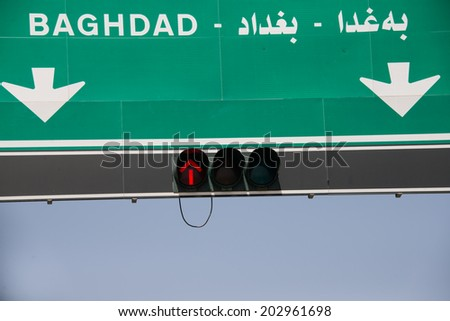 ERBIL, IRAQI KURDISTAN - JUNE 21: A road sign points toward Baghdad in the city of Duhok, Ninevah Province, Iraqi Kurdistan, June 21, 2014 - stock photo