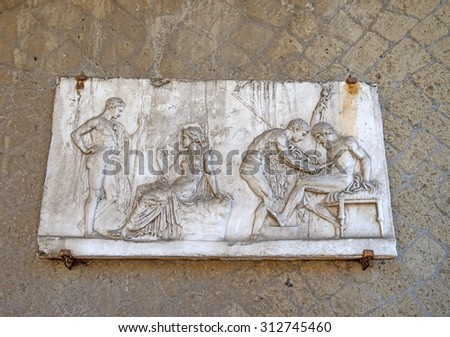 ERCOLANO, ITALY-JUNE 24, 2015: marble bas relief sculpture on the archeological site of the Roman Emperor's town of Ercolano preserved after the eruption of the Vesuvio volcano on 79dc, in Ercolano. - stock photo