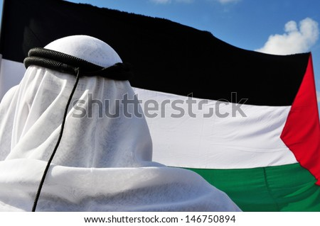 EREZ CROSSING-DECEMBER 31:Palestinian man against the Palestinian flag on Dec 31 2009.On April 2013, 132 (68.4%) of the 193 member states of the United Nations have recognized the State of Palestine.