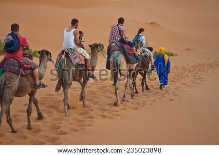 ERG CHEBBI, MOROCCO - AUGUST 4: Camel caravan with tourists in the desert on August 4, 2010 in Erg Chebbi, Morocco. Erg Chebbi is part of Sahara desert. - stock photo