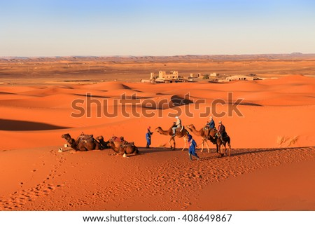 ERG CHEGGI, MOROCCO - FEBRUARY 28, 2016: People riding on a caravan of camels towards the dunes of the Sahara Desert at Erg Cheggi, Morocco at sunset