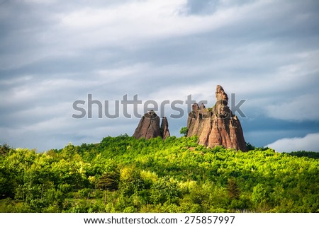 Eroded sand rock over green forest and dramatic sky background
