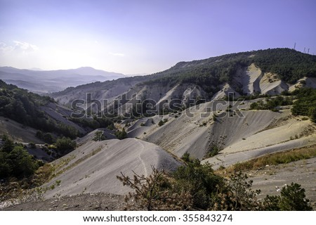 erosion and pine forest under blue sky - stock photo