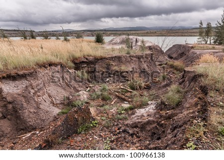 erosion furrow with water influent into man-made lake after mining - stock photo