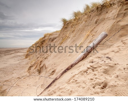 Erosion in the dunes. A landslip  and fallen barbwire fence caused by heavy storms on the north sea coast - stock photo