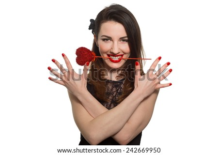 Erotic looking woman with red lipstick holding Valentine heart in her mouth teeth. Showing red nails in black dress - stock photo
