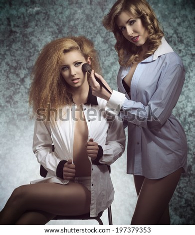 erotic portrait of two sexy girls with open shirt and creative hair-style applying blush and posing with naked legs
