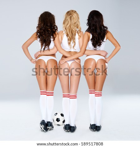 Erotic view of a row of sexy female buttocks as three sexy shapely women in lingerie and soccer boots stand arm in arm flaunting their bottoms to the camera