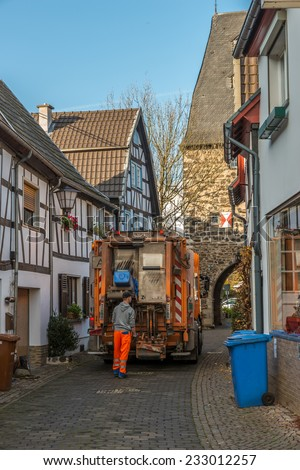 ERPEL, GERMANY 24 NOVEMBER, 2014 - Unidentified person emptying the bins, the job is carried out every monday in this peaceful village