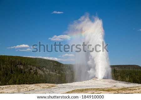 Errupting Old Faithful Geyser in Yellowstone National Park with rainbow.