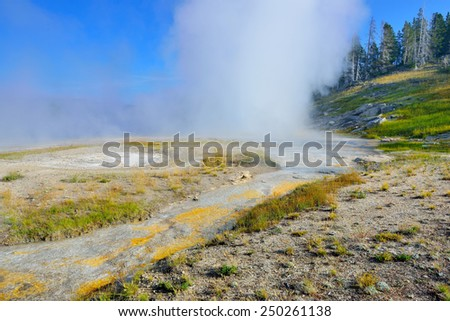 erupting Grand Geyser in Upper Geyser basin of Yellowstone National Park, Wyoming - stock photo