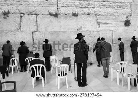 ERUSALEM, ISRAEL - MARCH 29, 2015 : Jewish worshipers pray at Wailing Wall in Jerusalem after sunset, Israel  - stock photo