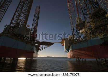 "ESBJERG, DENMARK - NOVEMBER 27 2016: Oil rig ""Maersk Resolute"" and ""Maersk Giant"" with a small wind farm on Fano Island in the background.  November 27 in Esbjerg, Denmark."