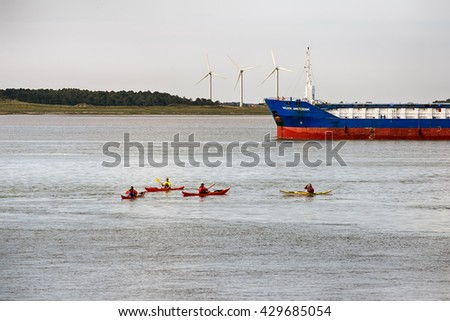 ESBJERG - MAY 28: Cargo boat close to Esbjerg harbor. Kayaks on tour and windmills on Fanoe Island in the background on May 28, 2016 in Denmark. - stock photo