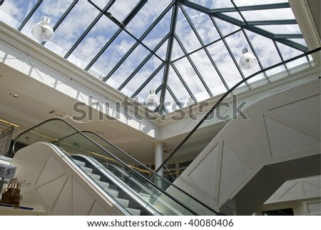Escalator in a mall with glass roof - stock photo