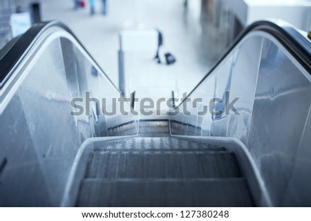 Escalator in airport. Tilt-shift lens used to accent the stairs and sublime blue cast applied for more business effect - stock photo