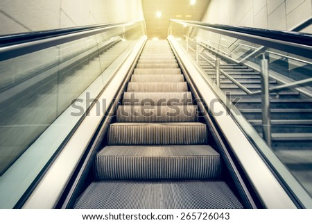 escalator with a bright light at the top