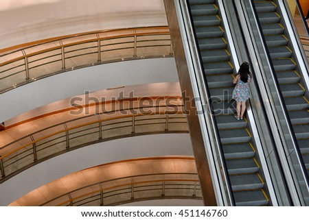 Escalator with people stand in the middle - stock photo